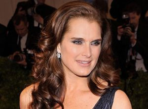 Brooke Shields in Tiffany diamond earrings, a diamond and pearl ring, and a clutch in navy leather