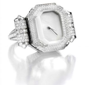 Ring watch by Steven Grotell in 18K white gold. Rock crystal center stone with pave diamond lunette and mother of pearl dial. Full pave diamond case body, side roundels' and ring shank highlighted by four briolette diamond cap stones. 347 diamonds with a total weight of 3.70 cts.
