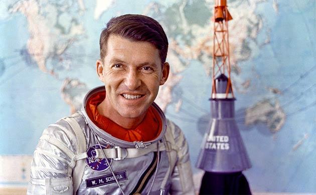 Astronaut Walter M. Schirra Jr. in Mercury pressure suit with model of Mercury capsule behind him.