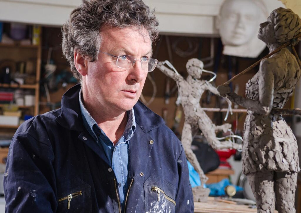 David Williams-Ellis studying one of his clay models