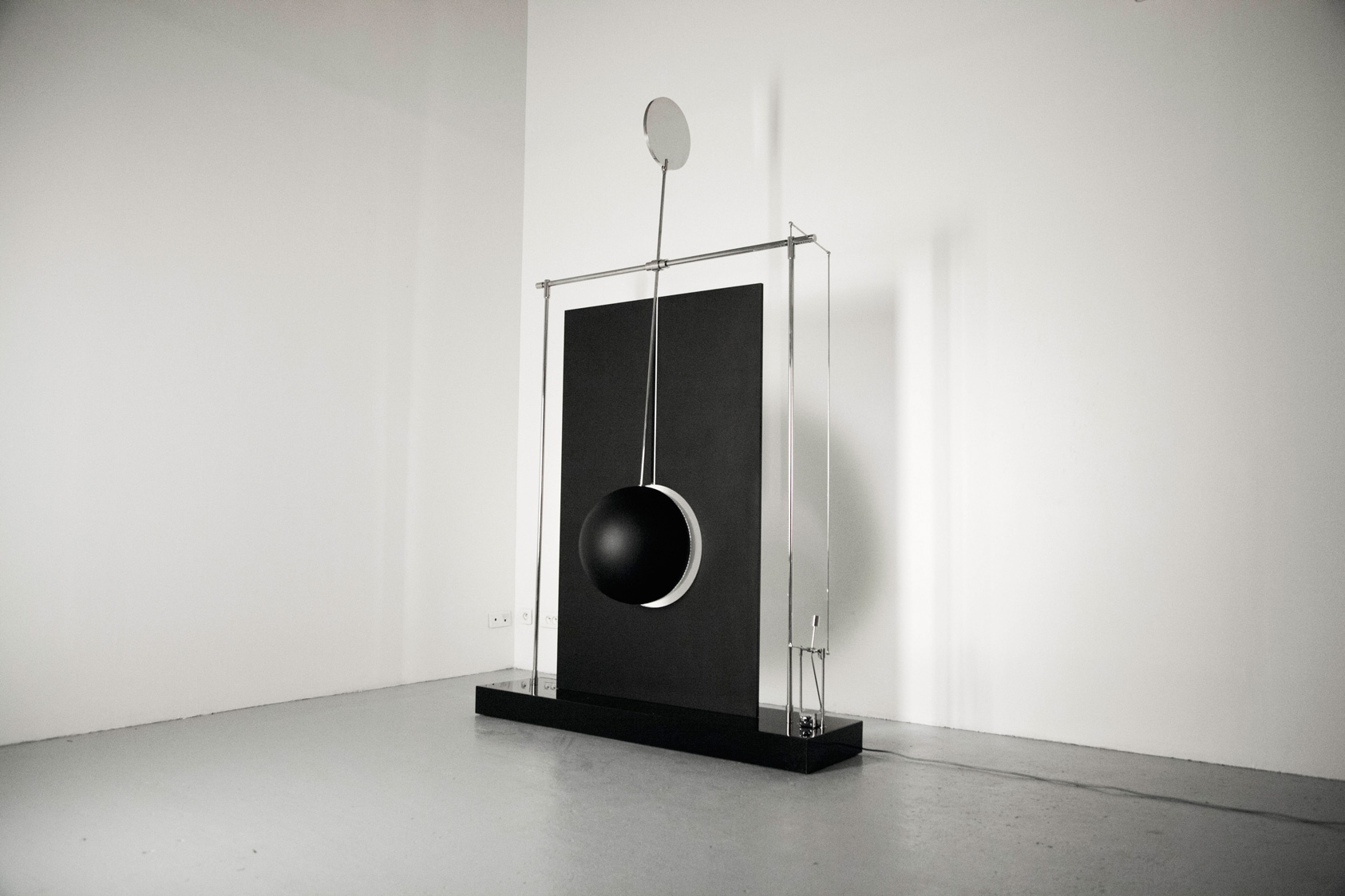 """In """"Spatial Variations"""", a slowly undulating metal ball ticks along its defined course, while throwing light and shadows on the surrounding space, almost as if the light is alive and breathing."""