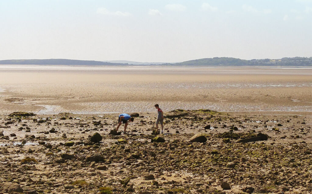 Two young boys checking the rock pools in the vast sandy bay