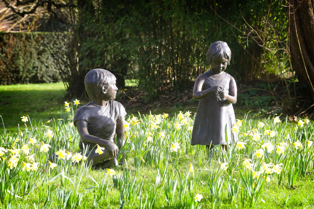 Photo showing statues of a young boy and young girl in the garden