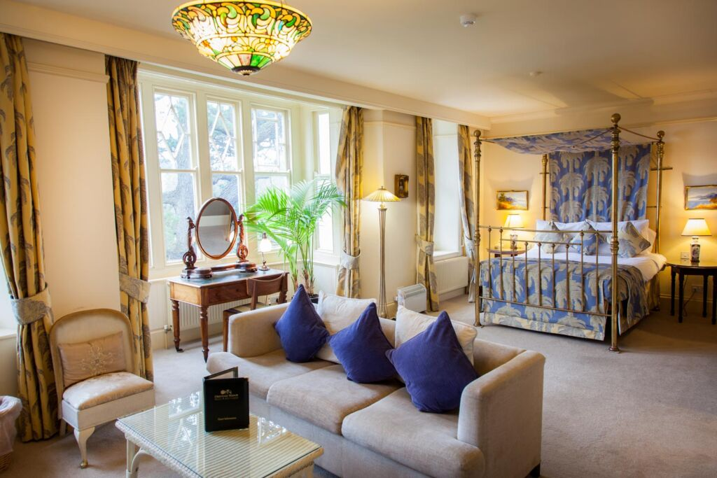 One of the large bedroom suites with lounge area and brass four poster bed