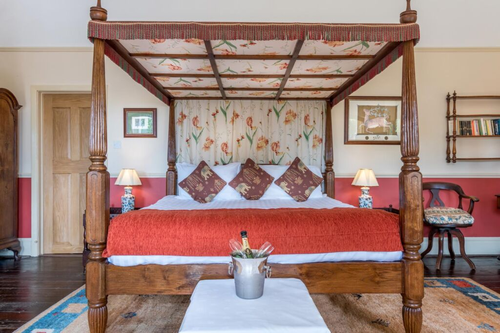 A wooden four poster bed at Orestone Manor in Devon