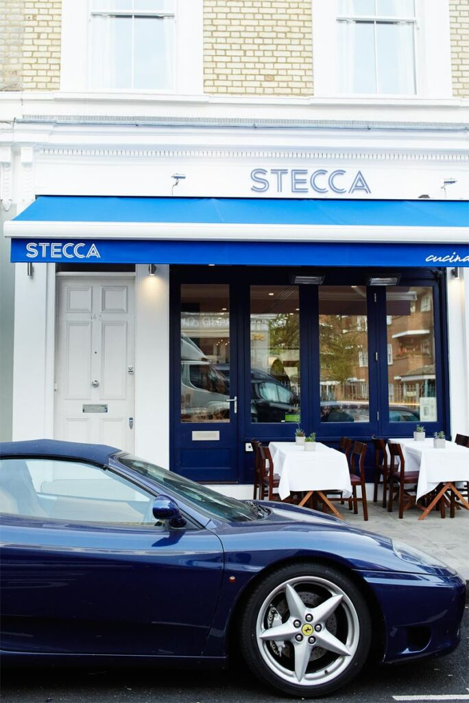 A dark blue Ferrari paked outside the front of Stecca