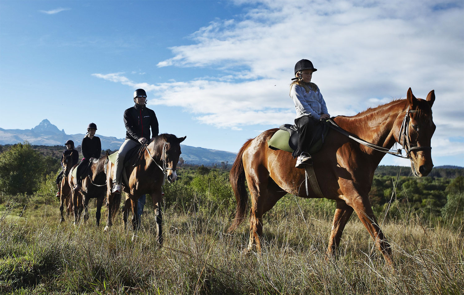 Picture of a family trekking on horses on the open plains