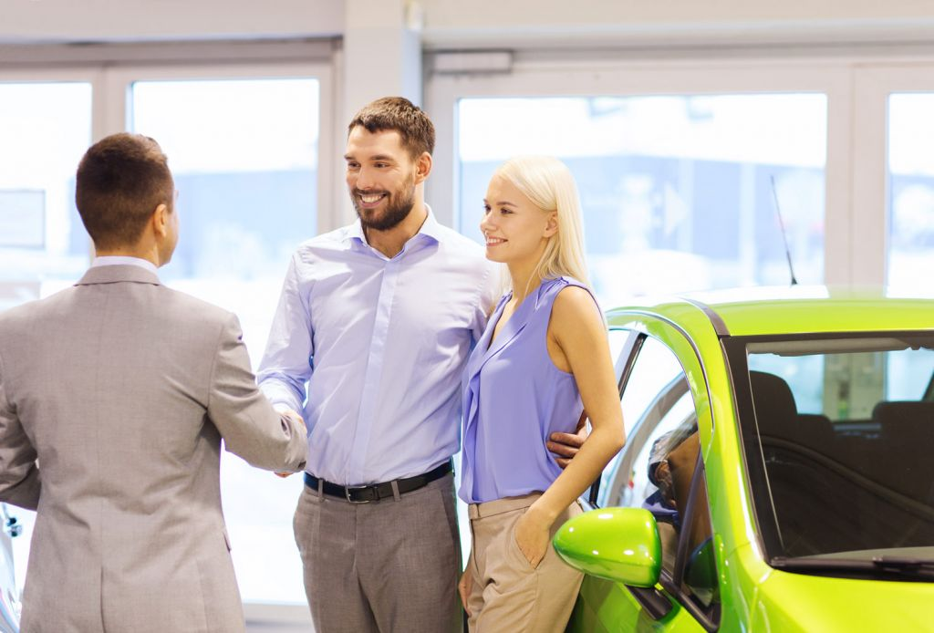 Couple buying a car from a dealer