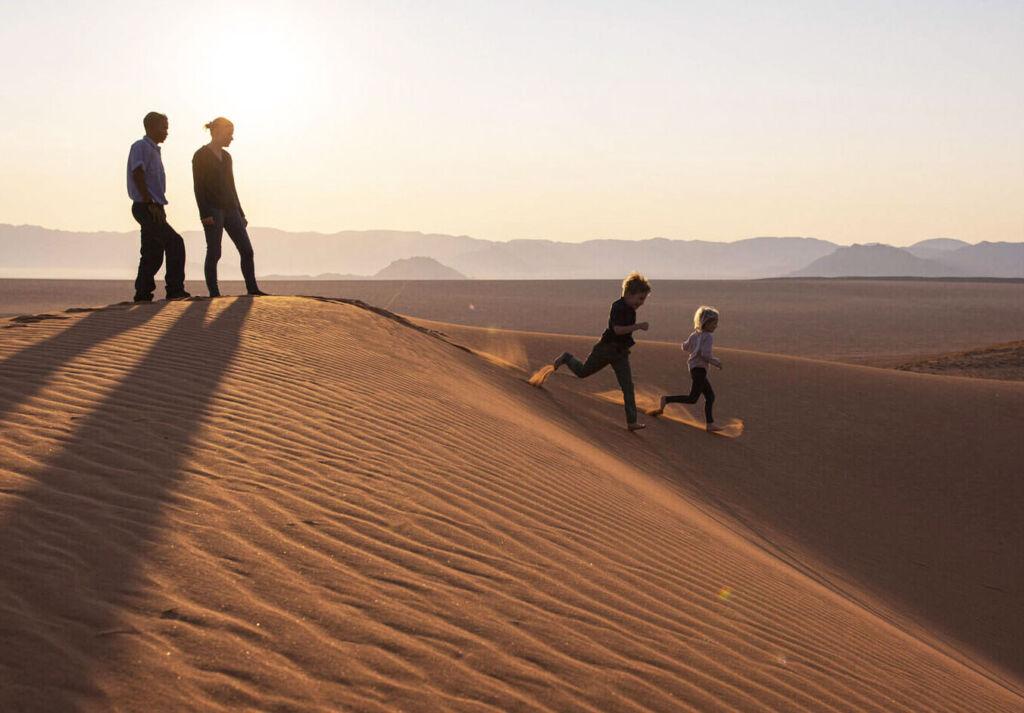 Children running down the dunes at Kwessi