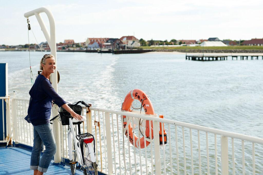 Woman taking her bike on a ferry in Jutland, Denmark