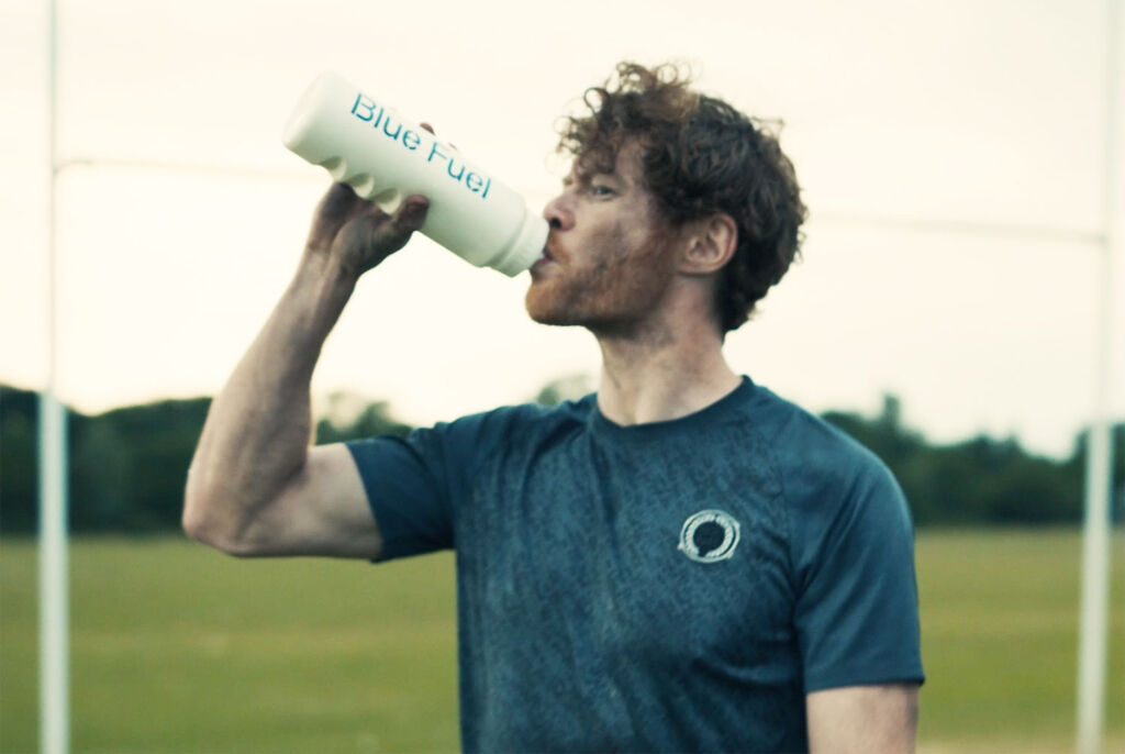 Male athlete drinking blue fuel