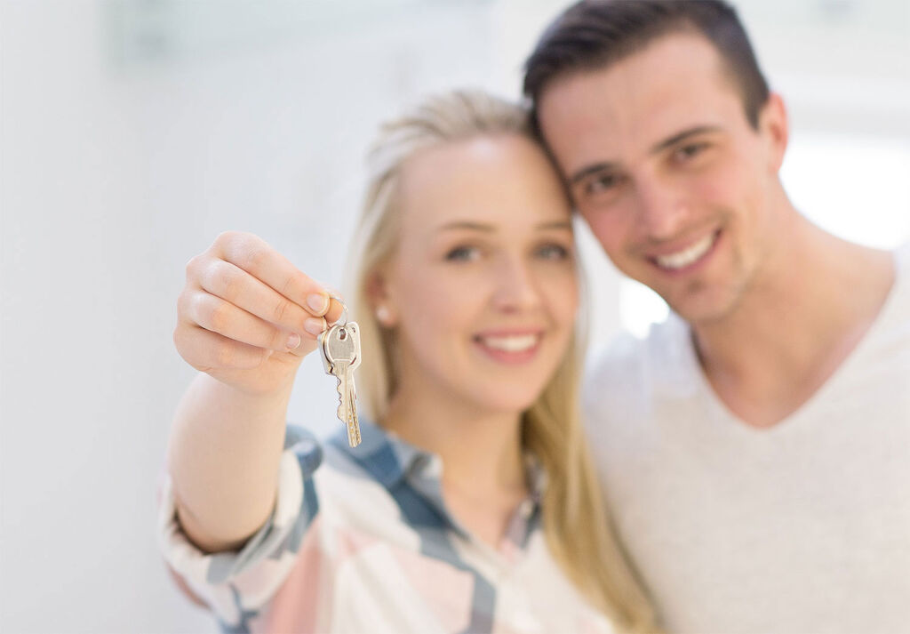 Young couple getting the keys to their first home