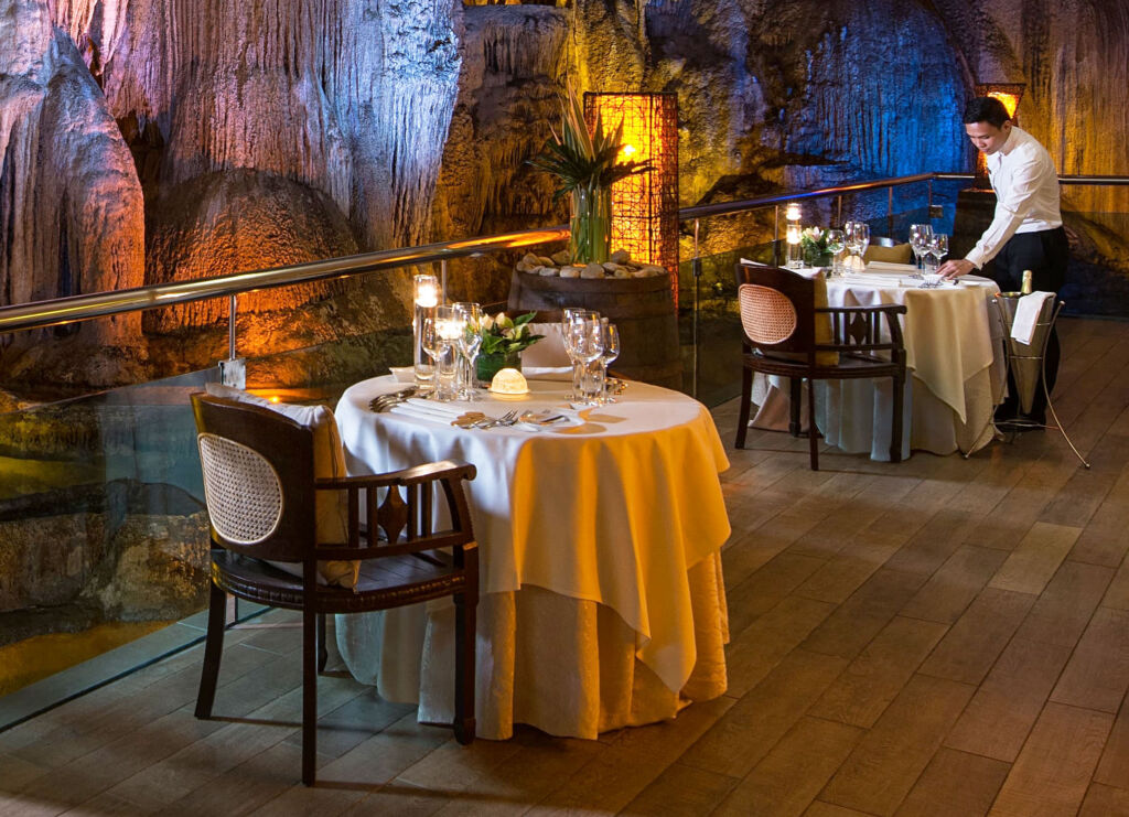 Waiter setting the tables for Cave Dining at the Banjaran