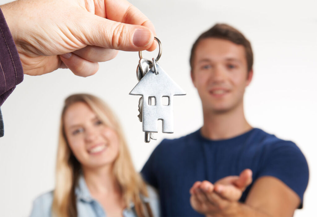 Young couple getting keys to first property