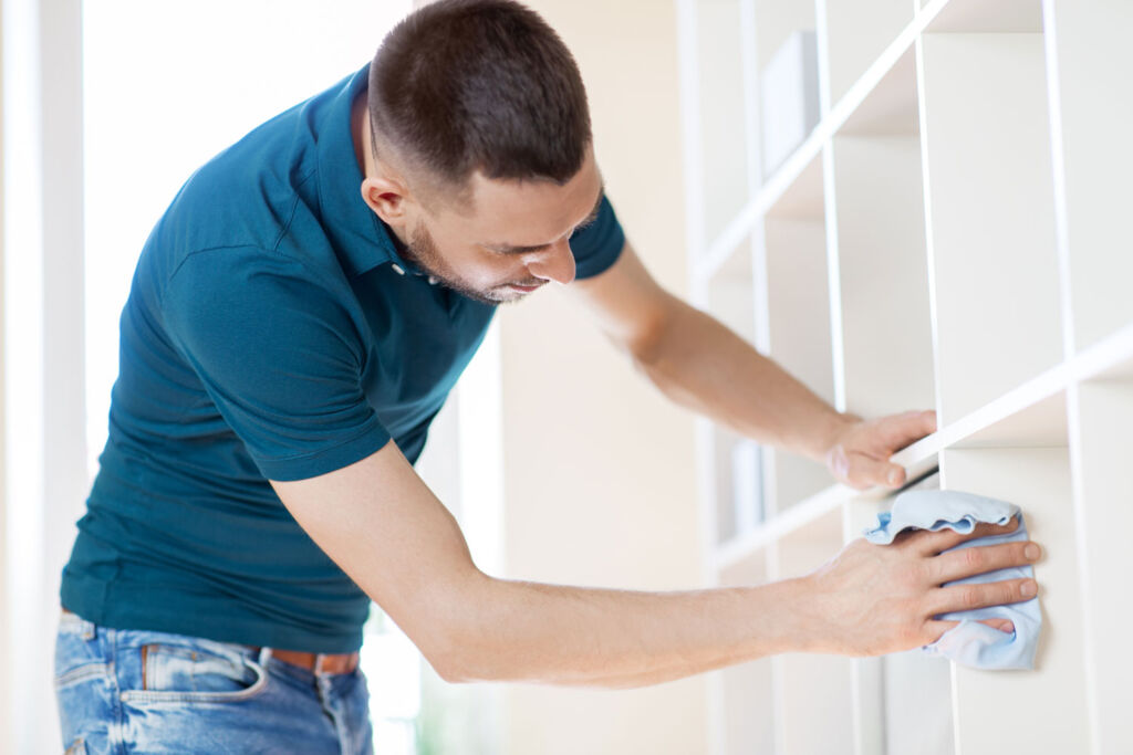 Man cleaning the shelves to make it ideal to list on the market