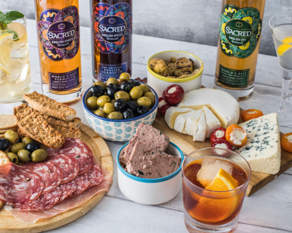 Bottles of Sacred Spirits Vermouth on a table of food