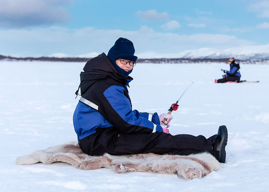 Ice fishing on a lake in Lapland