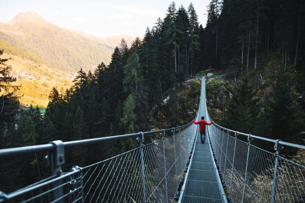 Person walking across a narrow bridge in Val di Rabbi. Photo by Simone Modino.