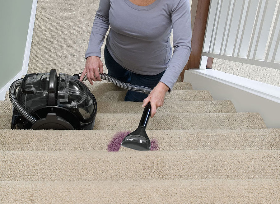 A woman using the machine to remove a stain on the stairs