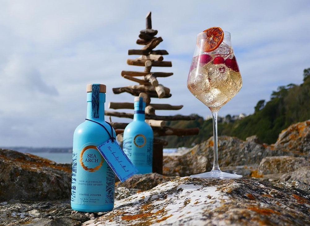 Bottle of Sea Arch Coastal Juniper on the rocks by the sea