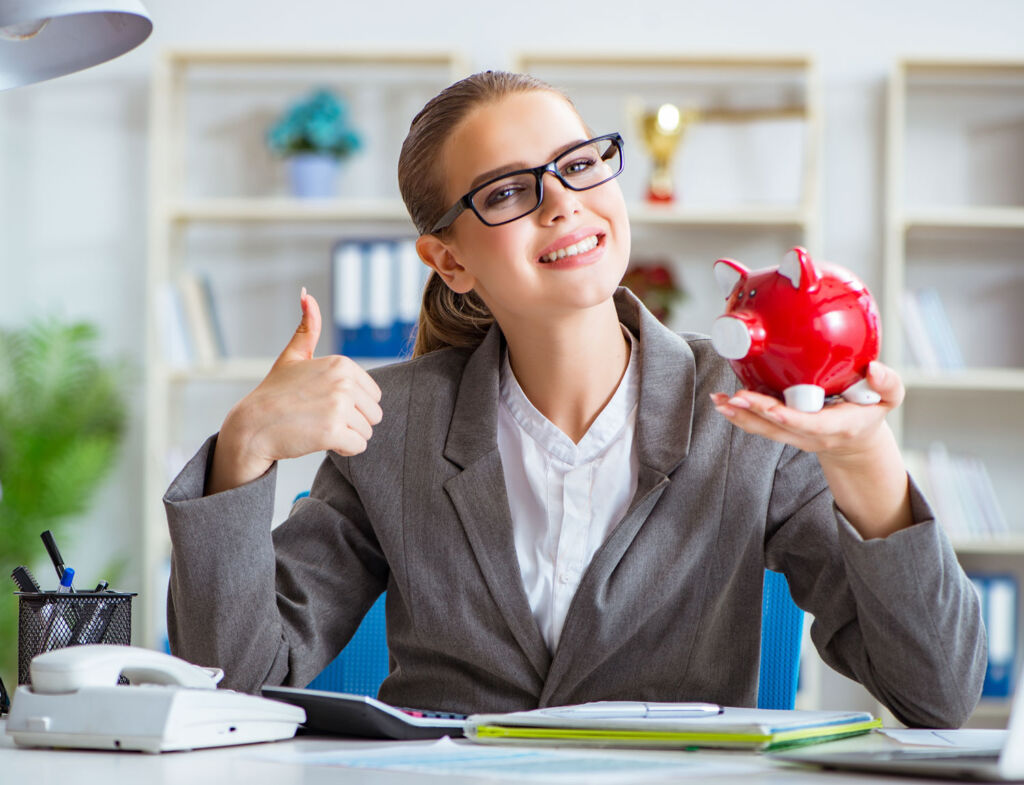 Woman in a bank holding a piggy bank