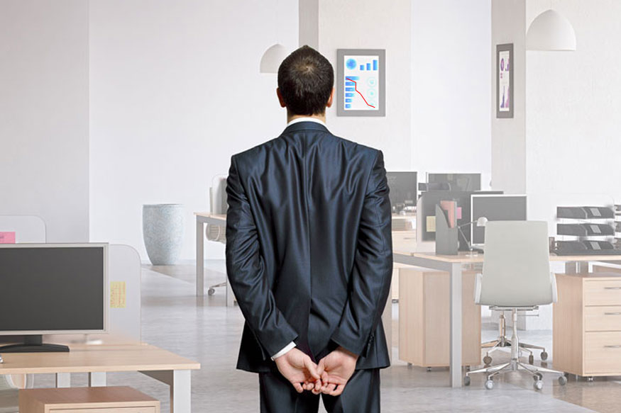 Boss looking at empty desks in the office