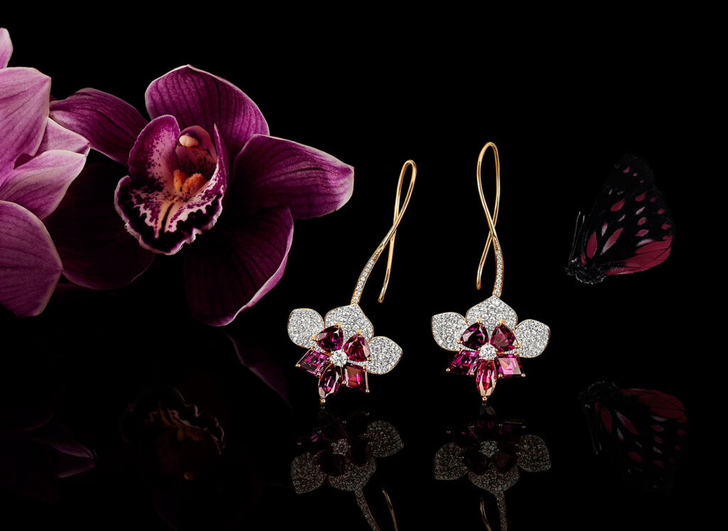 Amaranthine Orchid Earrings next to an orchid with a buttefly flying past