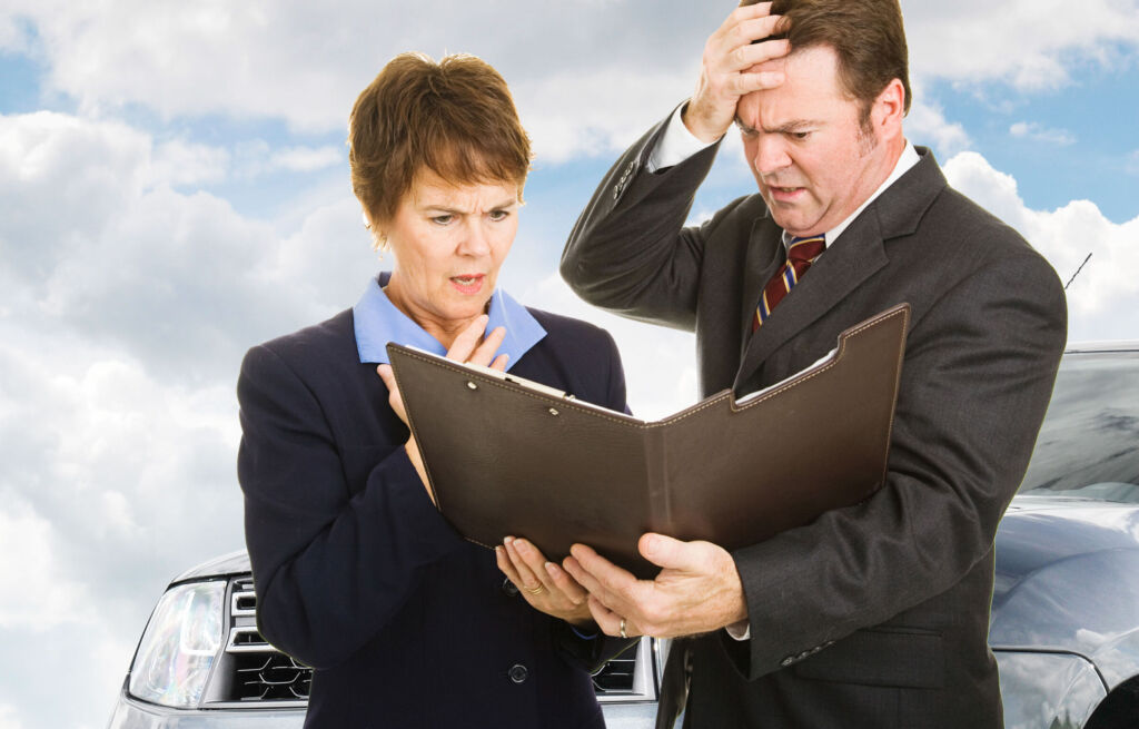 Male and female car salespeople looking at new car sales data