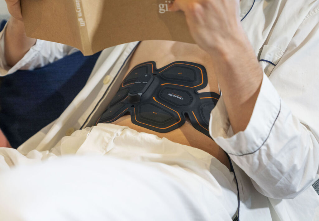 SIXPAD Abs Belt being worn by someone reading in bed