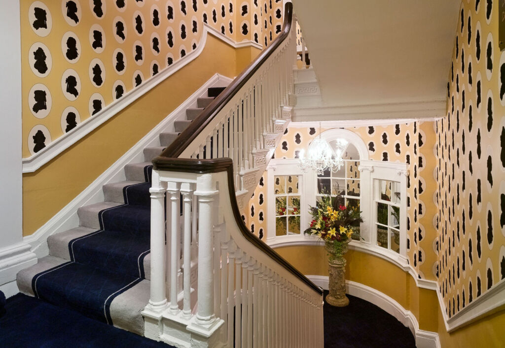 The main staircase is dressed with wallpaper showing silhouettes of people from different eras.