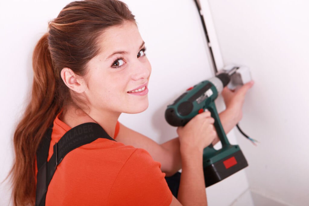 A woman using a cordless drill to put a socket on the wall