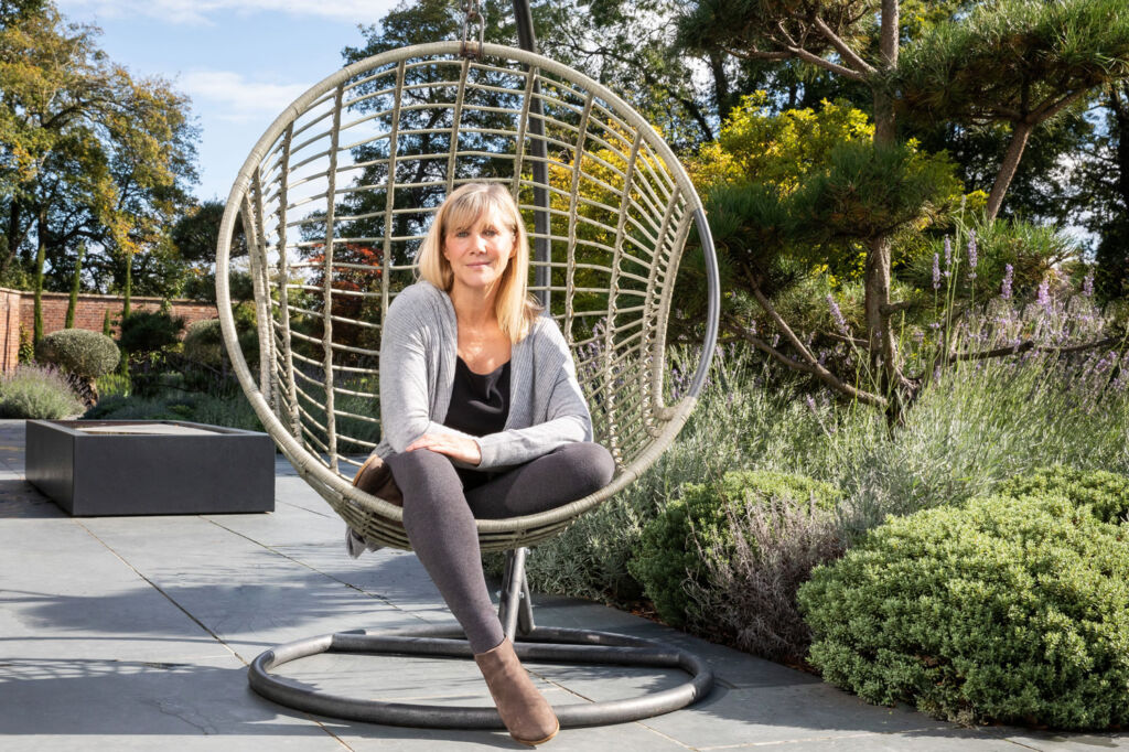 Breathing coach Rebecca Dennis sat in the garden on a swing chair