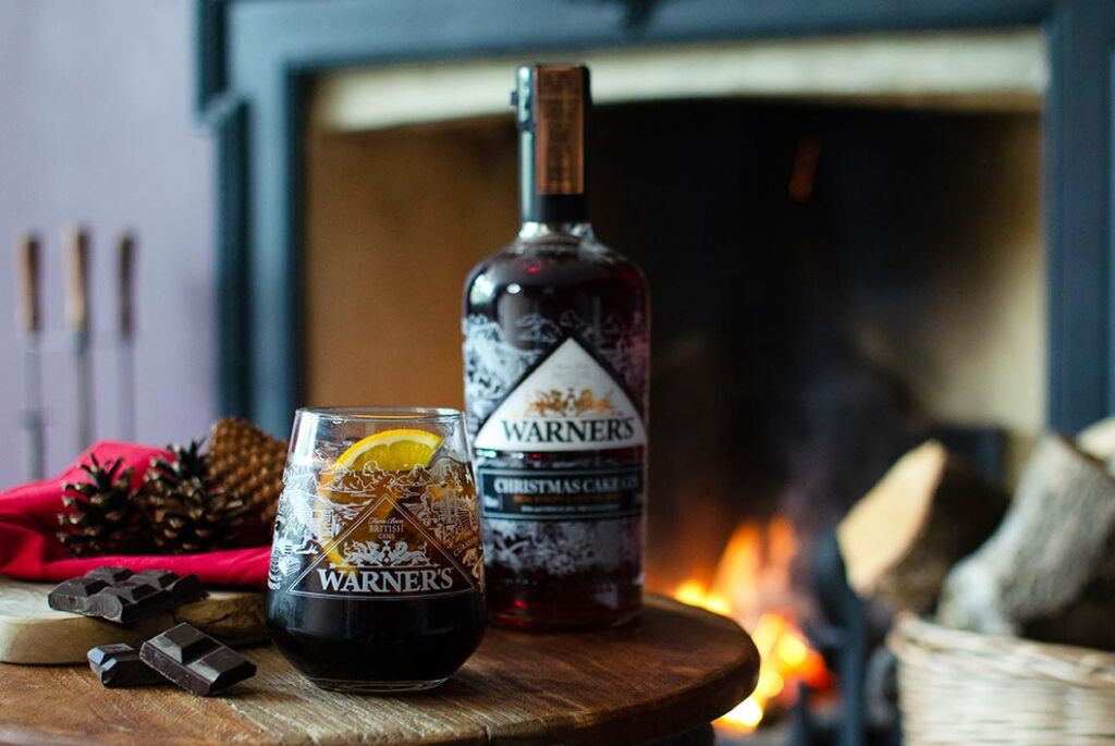 A bottle of the Christmas Cake Gin with freshly poured glass by a roaring fireplace