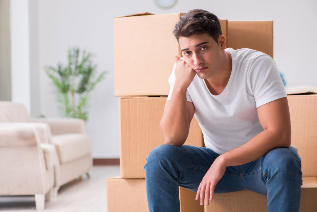 Man sat by some moving boxes looking miserable