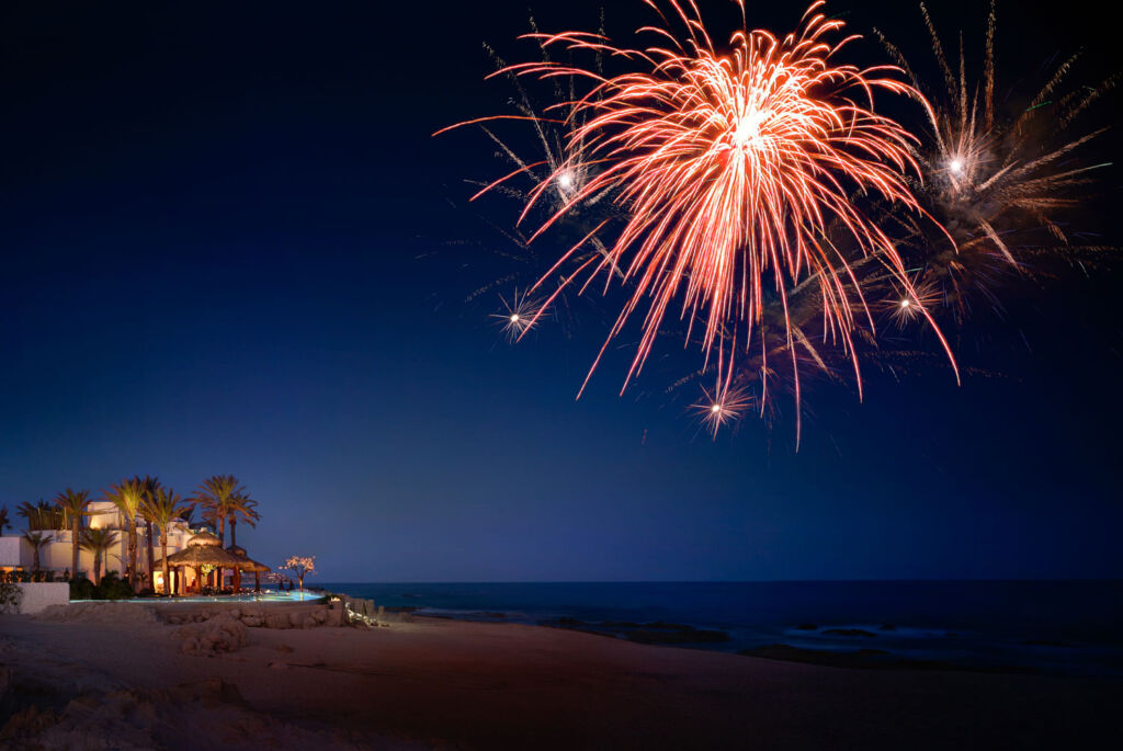Fireworks over a beach with a beautifully lit lone villa