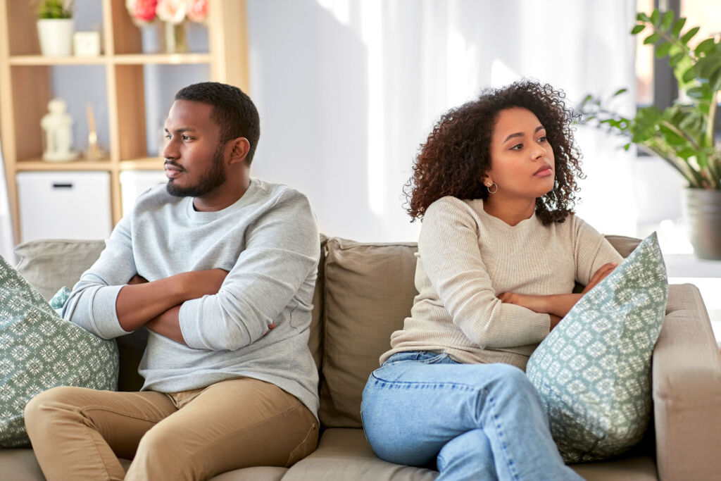 Couple disagreeing sat on a sofa