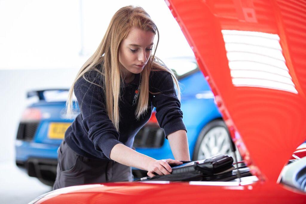 A female mechanic prepping a Ferrari