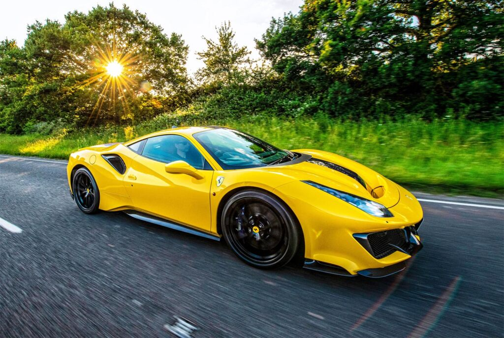 A yellow Ferrari supercar being driven in the English Countryside