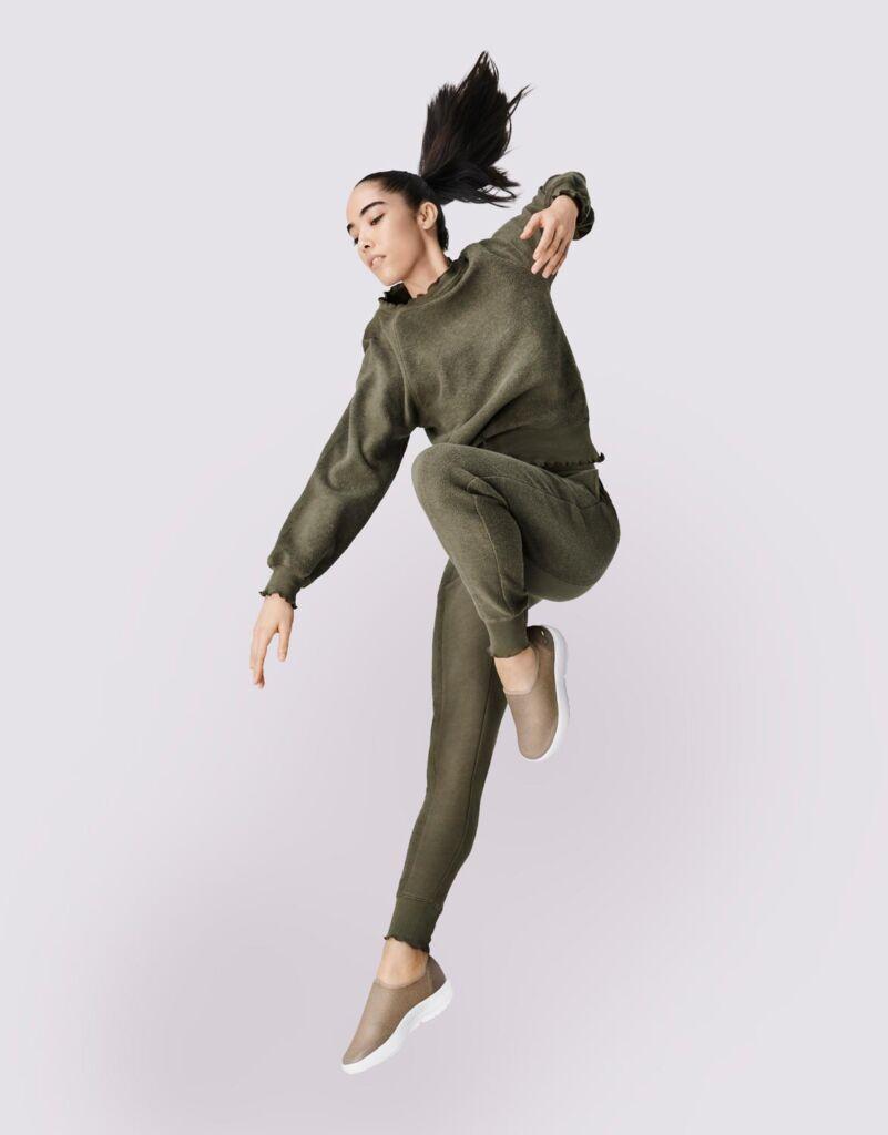 An energetic dancer wearing OOFOS shoes