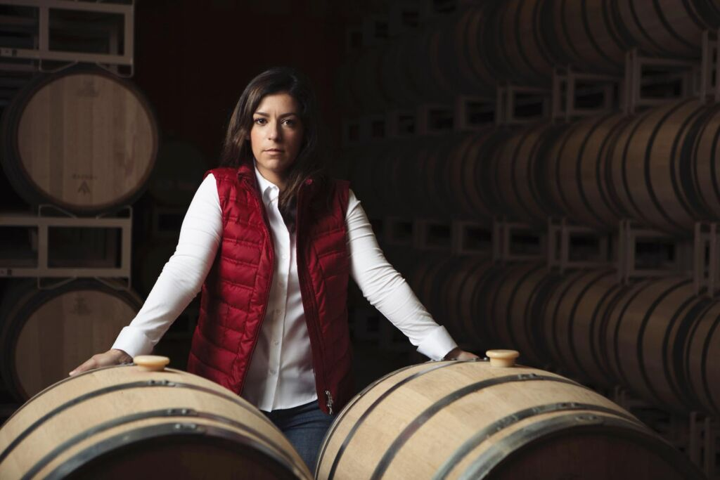 Hélène Seillan standing by some barrels