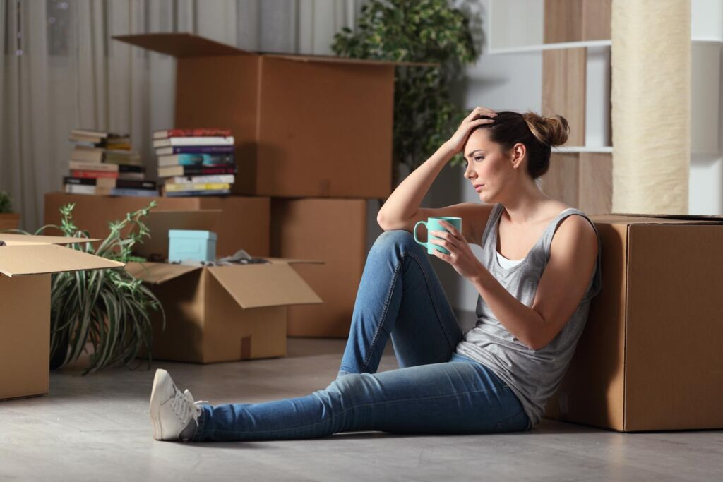 A woman sat on the floor, stressed over moving home