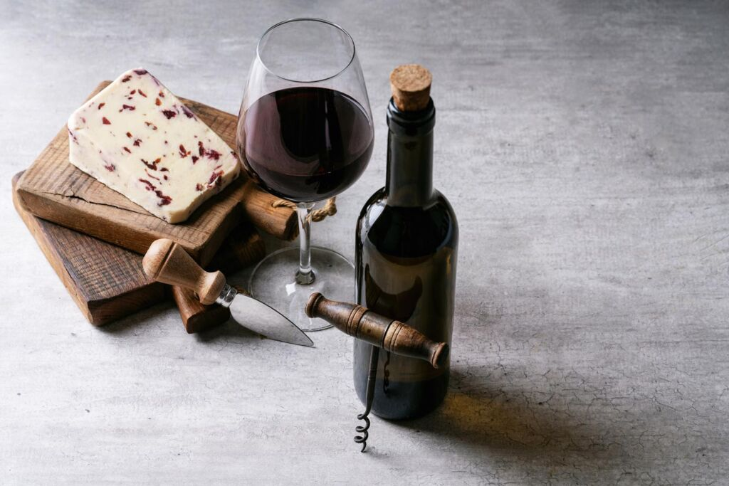 A bottle and glass of wine with some cheese