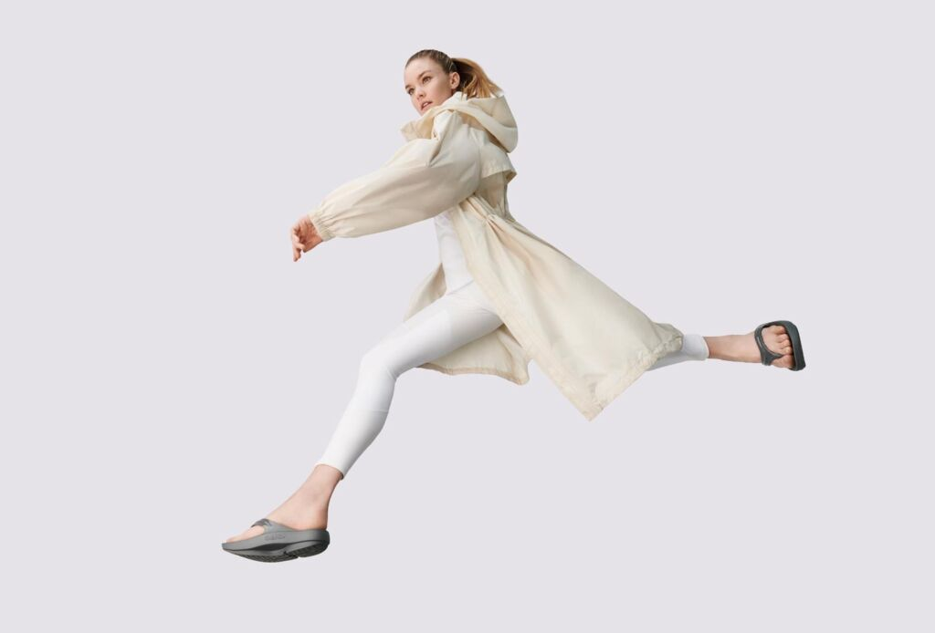 Young woman jumping in the air in OOFOS flipflops