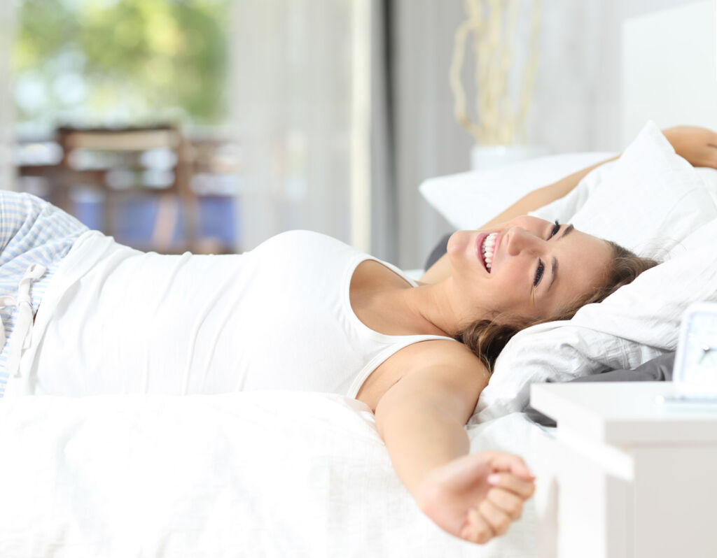 A woman waking up in bed after an excellent nights sleep