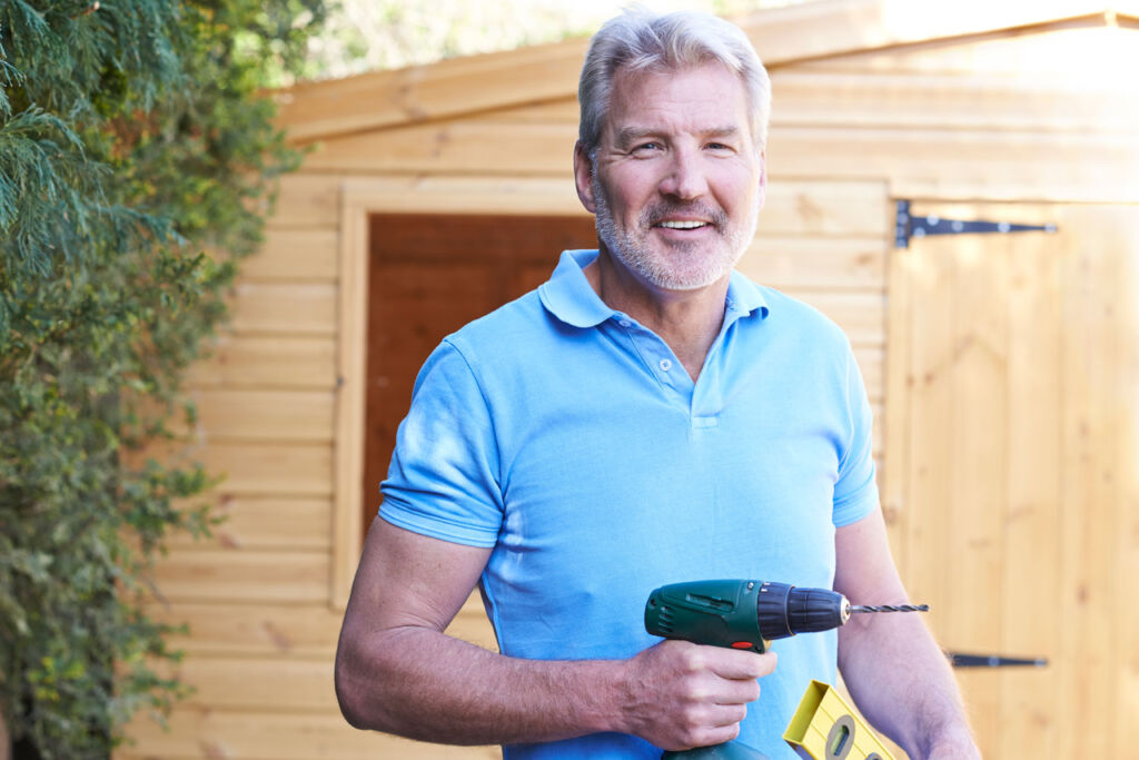 A man holding a drill looking very pleased after constructing a shed in the garden