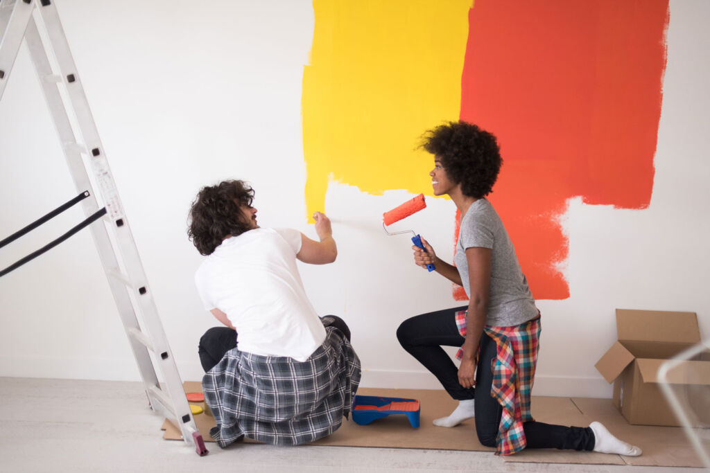 Couple decorating their home with bright coloured paint