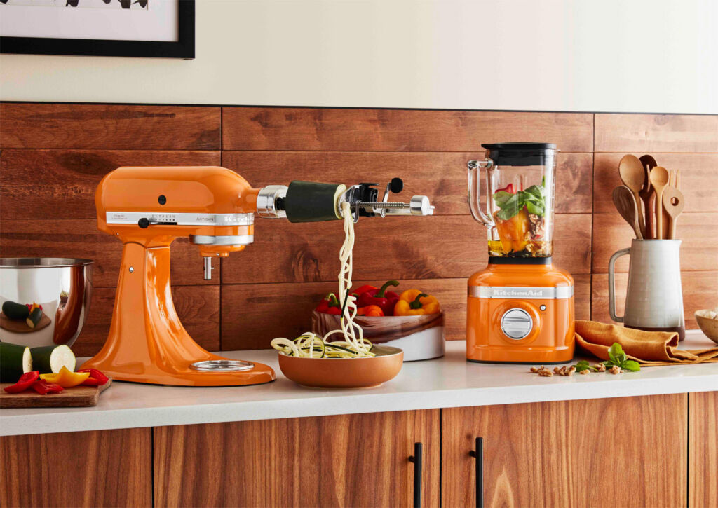 KitchenAid's Artisan mixer and blender in Honey colour on a kitchen worksurface
