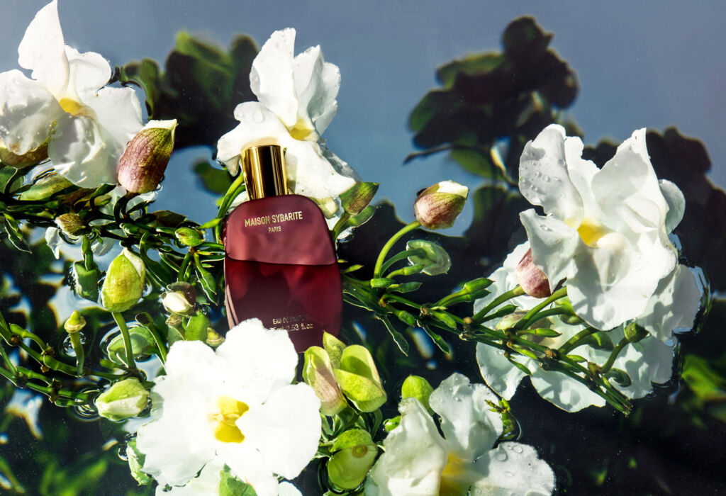 A photo showing the a fragrance bottle immersed in water among flowers