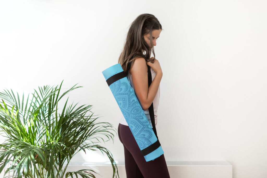 A young woman carrying a rolled yoga mat over her shoulder