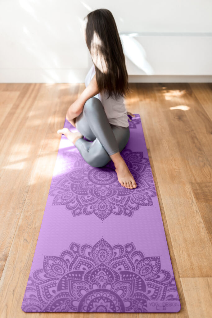Young lady performing a yoga pose on a purple floor mat
